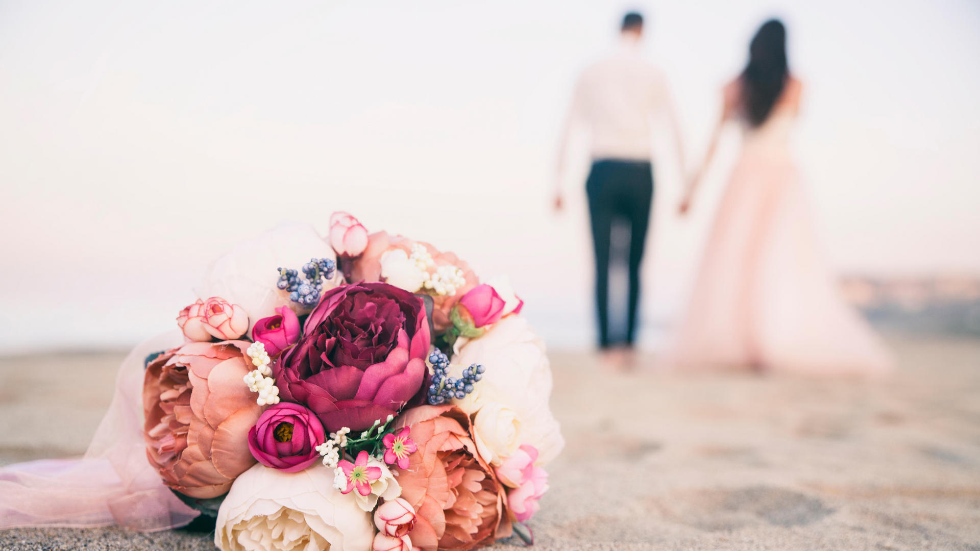 couple walking hand in hand on beach with flower boquet laying on sand